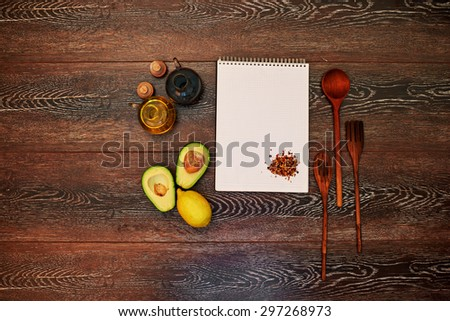 Cook writes in a notebook new recipes for a cookbook, avocado sauce with olive oil - stock photo