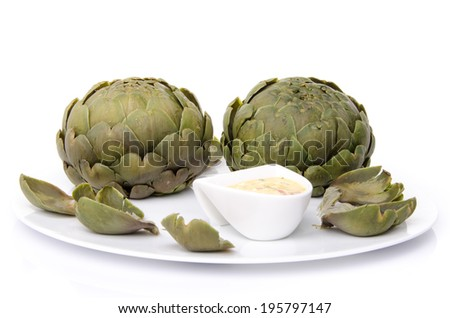 Cooked artichoke with a vinaigrette sauce on a plate, isolated on white - stock photo