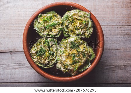 Cooked artichokes with parsley and parmesan, served in a clay dish on a wooden table - stock photo