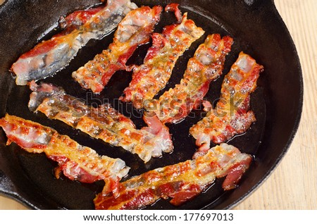 Cooked bacon rashers on a skillet. Selective focus - stock photo