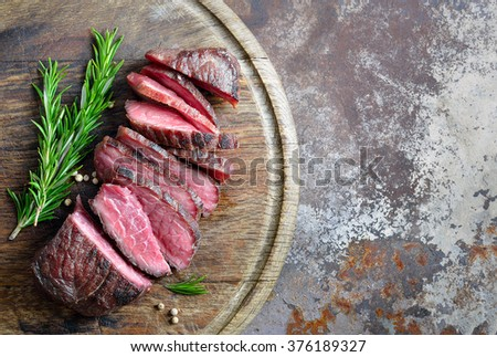 Cooked beefsteak cut on a board, top view - stock photo