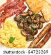 Cooked breakfast with scrambled eggs, bacon, sausages, sauteed mushrooms and hash browns. - stock photo