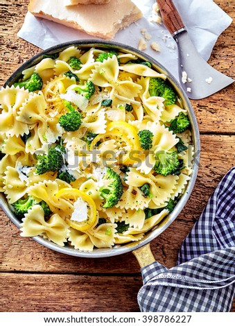 Cooked broccoli, parmesan and pasta in round steel pan with holder covered by blue and white napkin next to block of cheese - stock photo