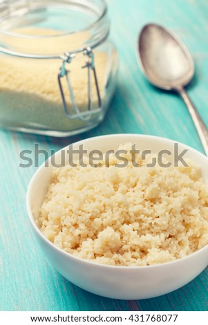 cooked couscous in a white bowl , couscous in a glass jar on a blue wooden background (Toning) - stock photo