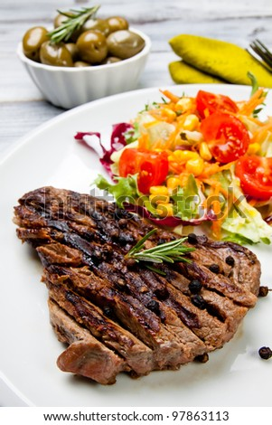 cooked cut of meat garnish with mixed salad - stock photo