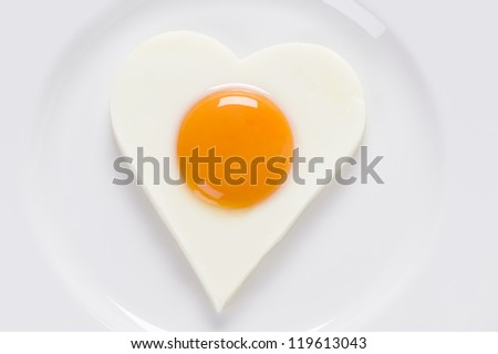 cooked egg sunny side up on a white plate view from above - stock photo