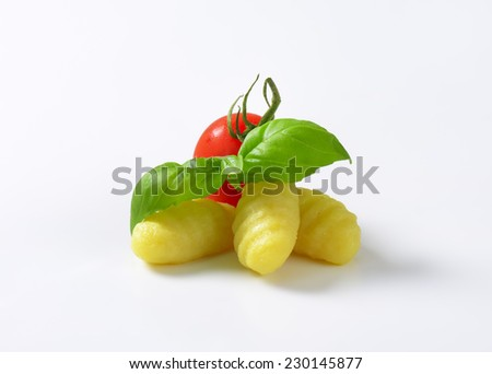 cooked gnocchi with cherry tomato and fresh basil on white background - stock photo