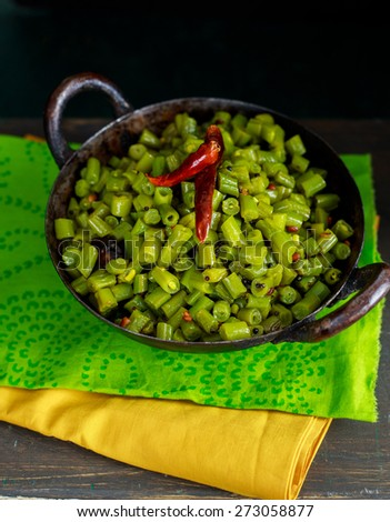 Cooked Green Beans in a Kadai is tempered with mustard seeds,urad dal and dried red chillies. It can be served as a SALAD or as a SIDE DISH or an accompaniment with Rice and Curry - stock photo