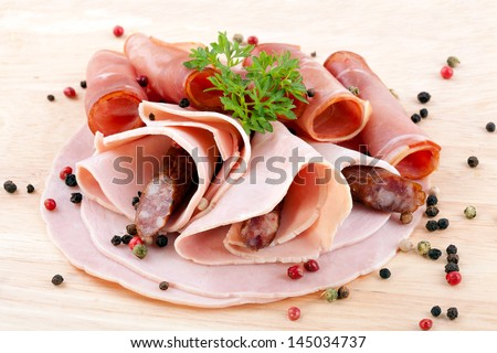 cooked ham, smoked ham and dried pork sausage served on wood with spices - stock photo