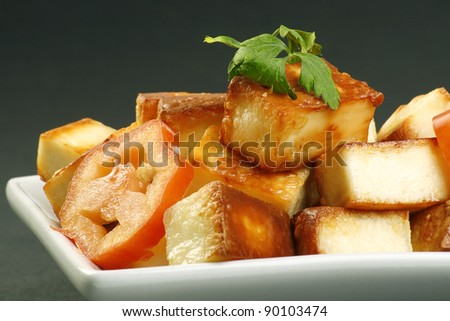 cooked indian paneer cheese and tomato on a grey background - stock photo