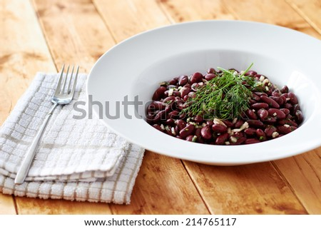 Cooked kidney beans on a white plate and wooden table  - stock photo