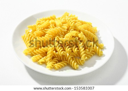 Cooked macaroni / a portion of cooked macaroni, served without sauce on white plate against a white backdrop  - stock photo