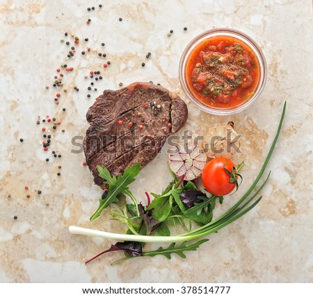 Cooked meat beef steak on the plate with spices, rosemary, onions and garlic on marble background, top view - stock photo