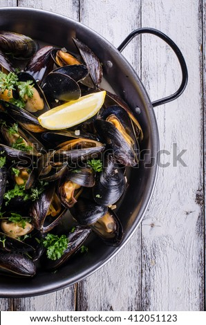 Cooked mussels in a pan on white wooden background - stock photo
