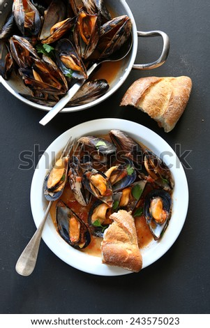 Cooked mussels in tomato sauce garnished with parsley.Top view - stock photo