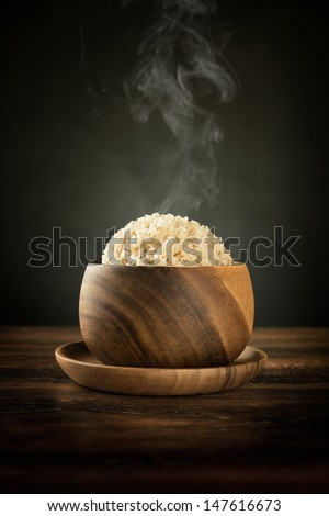 Cooked organic basmati brown rice in wooden bowl with hot steam smoke on dining table. Low light setting. - stock photo