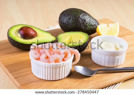 Cooked peeled shrimps with avocado and white sauce on wooden plank - stock photo