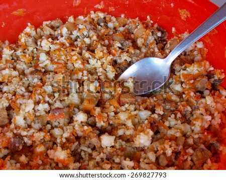 Cooked pilaf in red plastic bowl on the table     - stock photo