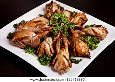 Cooked quail served on plate with parsley - stock photo