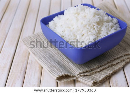Cooked rice in bowl on wooden background - stock photo