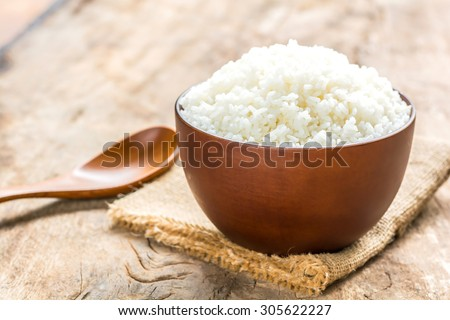 Cooked rice in bowl with spoon on old wooden table - stock photo
