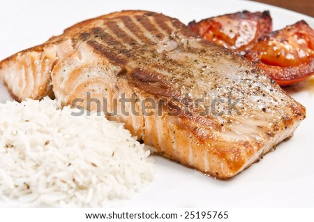 cooked salmon fillet on white plate with rice and tomato - stock photo