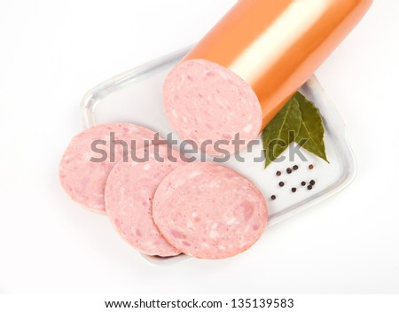 Cooked sausage, ham with slices on plate isolated on white background - stock photo