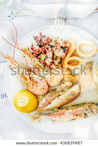 Cooked seafood on plate with lemon and wine. Prawns, squid, octopus, mullet fish and sea bream. Traditional Mediterranean dish on Greek island of Kastelorizo - stock photo