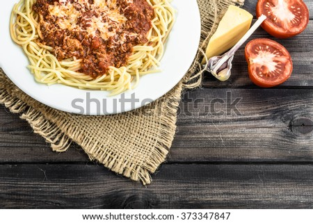 Cooked spaghetti bolognese and ingredients for cooking. - stock photo