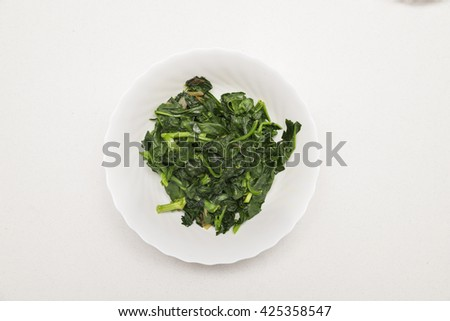 Cooked spinach with some onions on a white plate and table - stock photo