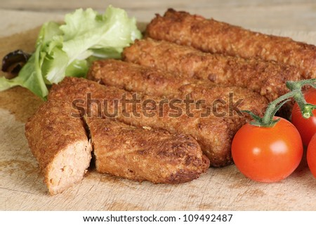 Cooked vegetarian sausage on a wooden board with lettuce and tomato - stock photo