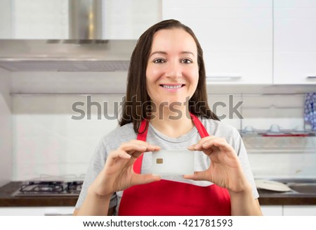 cooker woman showing credit cart in blank with copyspace at the kitchen as concept of domestic economy - stock photo