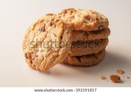Cookie : A stack of delicious homemade round milk chocolate chip macadamia cookie with a few crumbs on white - stock photo