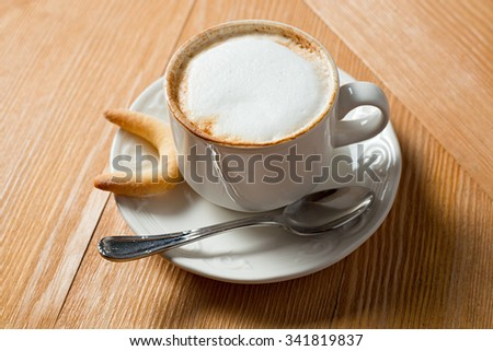 cookie and cup of coffee on wooden table - stock photo