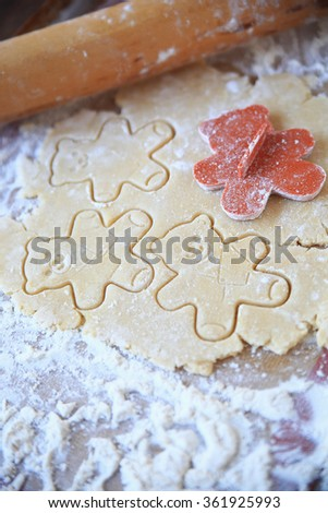 Cookie dough with teddy bear shapes and rolling pin on floured surface - stock photo