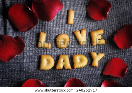 Cookies ABC in the form of word I LOVE DADDY alphabet with red rose petal on old jean background, Valentines day - stock photo