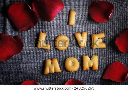 Cookies ABC in the form of word I LOVE MOM alphabet with red rose petal on old jean background, Valentines day - stock photo