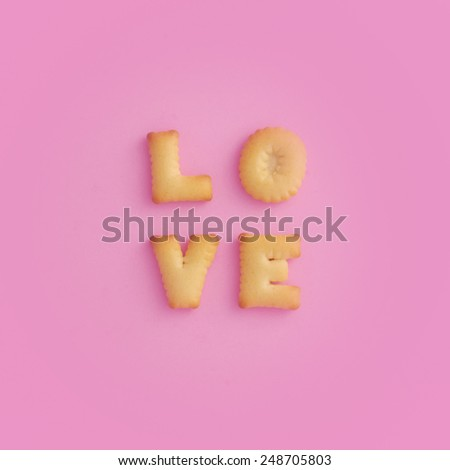 Cookies ABC in the form of word LOVE alphabet on pink background - stock photo