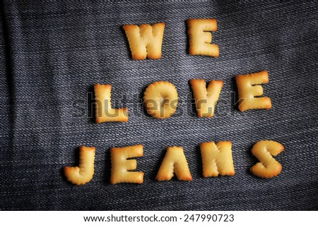 Cookies ABC in the form of word WE LOVE JEANS alphabet on old jean background, Valentines day - stock photo