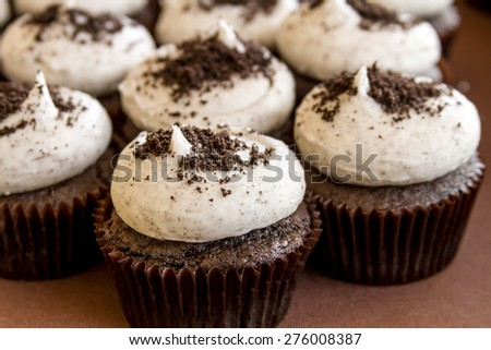 Cookies and cream chocolate cupcakes sitting on display table - stock photo