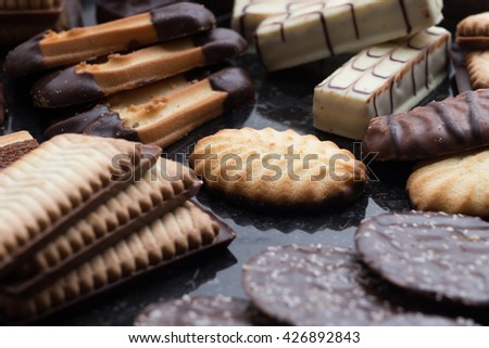 Cookies assorted on black background. Delicious morning snacks for breakfast, brunch and lunch. Appetizing, sweet and fast food - stock photo