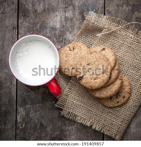 Cookies from above with milk cup on wooden table - stock photo