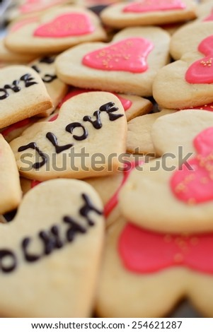 cookies in the shape of a heart with the word love in English and Polish - stock photo
