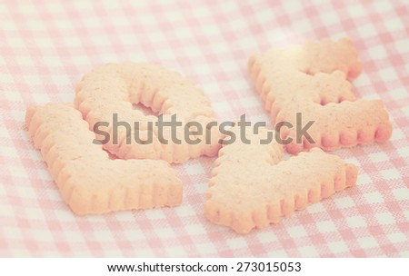 Cookies letters LOVE alphabet on pink background - stock photo
