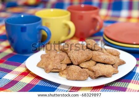 cookies on a plate with three cups and saucers - stock photo