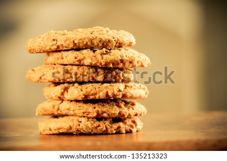Cookies - This is a stack of cookies shot on a wooden table top. Shot with a shallow depth of field and a warm retro color tone. - stock photo