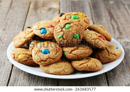 Cookies with colorful candy on plate on grey wooden background - stock photo