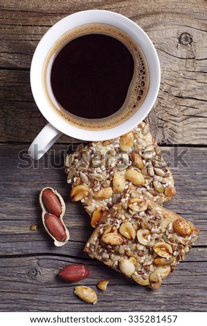 Cookies with nuts, seeds and coffee cup on old wooden table, top view - stock photo