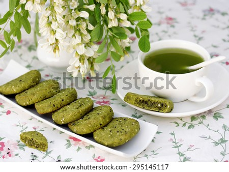 cookies with sesame and matcha tea, a cup of green tea and acacia in a vase - stock photo