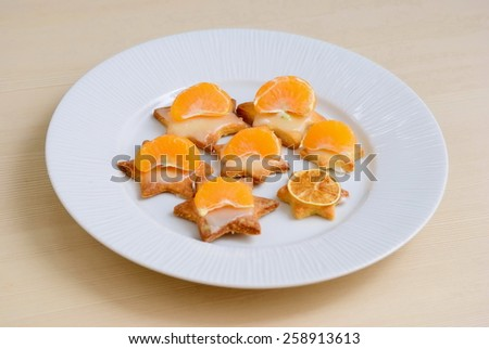Cookies with tangerines on a white plate - stock photo